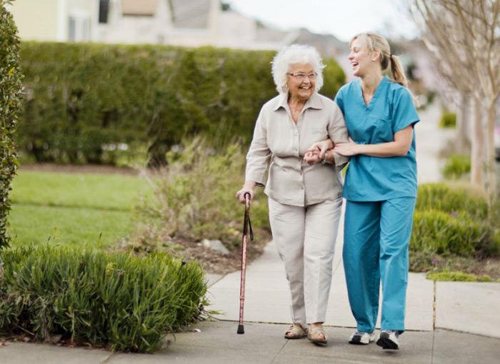 Сестра гуляет с больной после инсульта